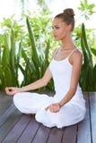 Young woman practicing yoga sitting meditating Stock Photo