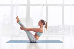 Young woman practicing yoga, sitting in Paripurna Navasana exercise at the yoga studio. Young woman practicing yoga, sitting in Paripurna Navasana exercise at stock image