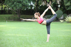 Young woman practicing yoga, standing bow pose on lawn Royalty Free Stock Photos