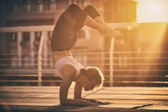 Young woman practicing yoga, standing in Vrischikasana Scorpion pose in the terrace at sunset Stock Photo