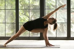 Young attractive woman in Utthita parsvakonasana pose, home back. Young woman practicing yoga, stretching in Extended Side Angle exercise, Utthita parsvakonasana Stock Photos