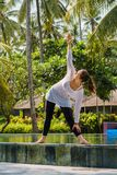 Young woman is practicing yoga in stretching position on the swimming pool with green plants, palm trees around in hotel