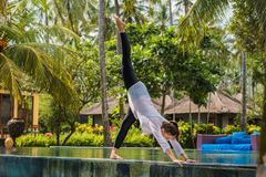 Young woman is practicing yoga in stretching position on the swimming pool with green plants and palm trees in hotel in Indonesia