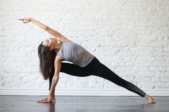Young attractive woman in Utthita parsvakonasana pose, studio ba. Young woman practicing yoga, stretching in Utthita parsvakonasana exercise, Extended Side Angle Stock Photography