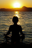 Young woman is practicing yoga at sunset. Young woman is practicing yoga on the sea beach at sunset Stock Images