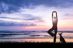 Young woman practicing yoga at beach on sunset. Silhouette of young woman practising yoga being one perfect harmony with nature at beach on sunset with her dog vector illustration