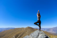 Young woman practicing yoga on top of the mountain Stock Photography