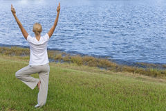 Young Woman Practicing Yoga By Tranquil Blue Lake. Rear view of a beautiful young blond woman practicing a yoga position by a tranquil blue lake royalty free stock photos
