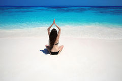 Young woman practicing yoga on the tropical beach with blue wate Royalty Free Stock Photos