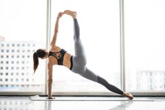 Young beautiful woman practicing yoga windows view in the background. Wellness concept. Calmness and relax, woman happiness. Young woman practicing yoga view in royalty free stock images