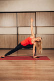 Young woman practicing yoga,-Virabhadrasana Rotated warrior pose royalty free stock photography