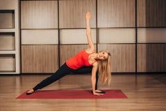 Young woman practicing yoga,-Virabhadrasana Rotated warrior pose royalty free stock photos