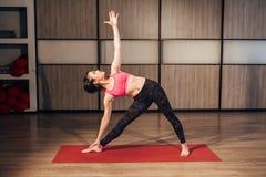 Young woman practicing yoga,-Virabhadrasana Rotated warrior pose stock image