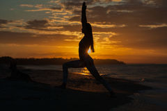 Young woman practicing yoga warrior and hero pose at sunset, sunrise . Zen wellness and wellbeing concept. Young woman practicing yoga warrior and hero pose at royalty free stock image