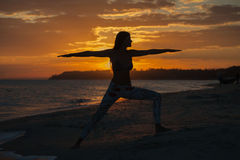 Young woman practicing yoga warrior and hero pose at sunset, sunrise . Zen wellness and wellbeing concept. Young woman practicing yoga warrior and hero pose at royalty free stock photography