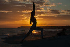 Young woman practicing yoga warrior and hero pose at sunset, sunrise . Zen wellness and wellbeing concept. Young woman practicing yoga warrior and hero pose at stock photography