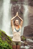 Young woman practicing yoga by the waterfall Stock Image