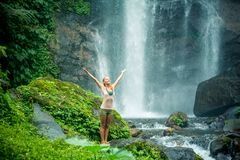 Young woman practicing yoga by the waterfall Stock Photo