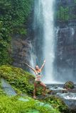 Young woman practicing yoga by the waterfall Royalty Free Stock Images
