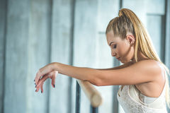 Young woman practising ballet. Take chance to lose yourself in dance. Cropped shot of attractive ballerina standing near ballet barre, putting her hands on it Stock Photos