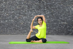 Young woman practising yoga. Portrait of young woman practising yoga pose on mat, Mermaid Pose Stock Images