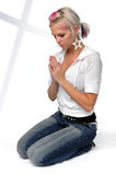 Young Woman Praying. Beautiful young woman praying with shadow on white wall Stock Photos