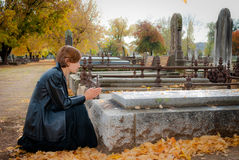 Free Young Woman Praying At Grave In Cemetery In Fall Stock Photography - 79200952