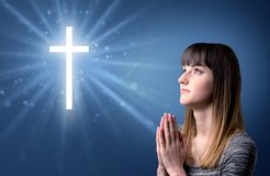 Praying girl. Young woman praying on a blue background with a sparkling cross above her Stock Photo