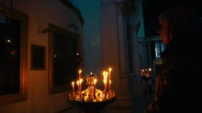 Young christian woman praying in the orthodox church in front of icons with candle light background. Slow motion. Young woman praying in the church in front of stock video footage