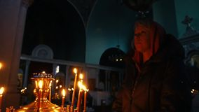 Young christian woman praying in the church in front of icons with candle light background. Slow motion. Young woman praying in the church in front of icons with stock video