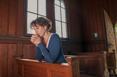 Young woman praying in the church stock photo