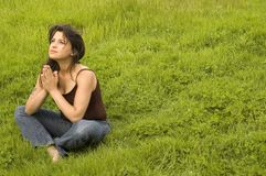 Young woman praying in a field. Young woman sitting in praying pose in a field of lush green grass, with the wind blowing through her hair royalty free stock images
