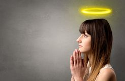 Praying girl concept. Young woman praying on a grey background with a shiny yellow halo above her head stock image