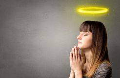 Praying girl. Young woman praying on a grey background with a shiny yellow halo above her head Royalty Free Stock Images
