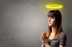 Praying girl concept. Young woman praying on a grey background with a shiny yellow halo above her head stock photos