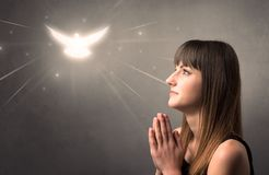 Praying girl. Young woman praying on a grey background with a sparkling bird above her Royalty Free Stock Photos
