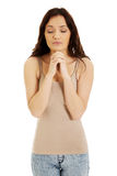 Young woman praying with her hands together. Stock Photo