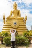 Young  woman praying and meditating Gold Buddha, Thailand, Phuket Royalty Free Stock Photography