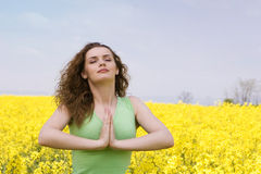 Young woman praying outdoors. Portrait of a young woman praying in rape flower field Stock Images