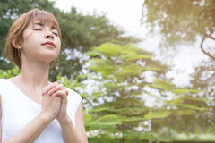 Young woman praying in public park. asian girl folded her hands Stock Image
