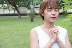 Young woman praying in public park. asian girl folded her hands Stock Photo