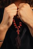 Young woman  praying with rosary in hand. Young woman  praying with rosary  in hand Royalty Free Stock Image