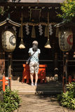 Young woman praying at Shinto shrine in Tokyo Stock Images