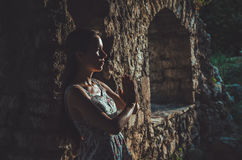 Young woman praying in Stari Bar old fortress, Montenegro. Girl silhouette on sunset. Religion, Meditating, Spirituality Stock Photo