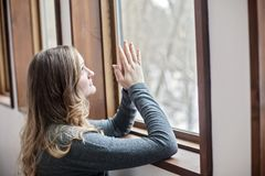 Young woman praying by window. A young woman kneeling and praying in a window sill Stock Photo