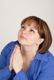 The young woman prays to god. Has prayerfully combined hands Stock Photo