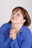 The young woman prays to god. Has prayerfully combined hands and closed eyes Stock Photo