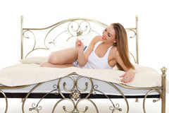 Young woman with pregnancy test. Happy young woman checking pregnancy test lays on a bed in the room. Positive result Stock Photos