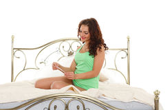 Young woman with pregnancy test. Happy young woman checking pregnancy test sits on a bed in the room. Positive result royalty free stock photography