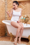 Young woman with pregnancy test. Unhappy young woman checking pregnancy test sits in a bathroom. Positive result stock photography